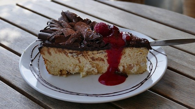 A plate with a piece of cake sitting on top of a wooden table